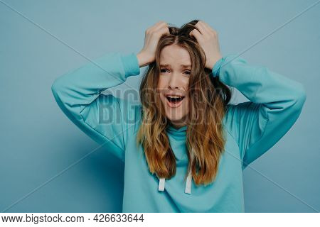 Pretty Young Female Expressing Shock And Disbelief While Holding Head, Screaming And Looking Away Fr