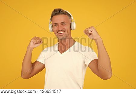 Music Is Power. Happy Man Flex Arms Yellow Background. Audio Power. Listening To Music. Headphones T