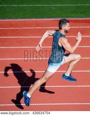Energetic Athletic Muscular Man Runner Running On Racetrack At Outdoor Stadium, Endurance