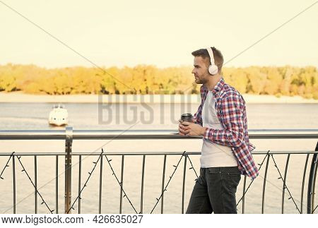 Good Morning Drink. Unshaven Guy With Coffee Cup Outdoor. Male Casual Hipster Fashion. Man In Headse