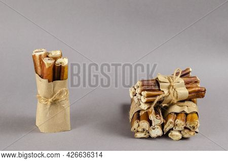 Bully Sticks For Dogs Wrapped In Brown Paper And Tied With Twine. Portioned Grouped Beef Pizzle For