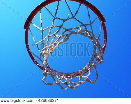Basketball Hoop With A Net Against A Cloudless Blue Sky. Closeup Photo From Bottom To Top