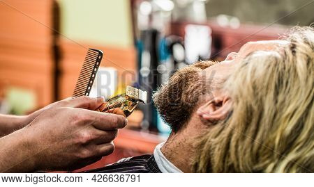 Barber Works With A Beard Clipper. Hipster Client Getting Haircut. Hands Of A Hairdresser With A Bea