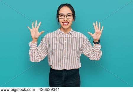 Young hispanic girl wearing casual clothes and glasses showing and pointing up with fingers number ten while smiling confident and happy.