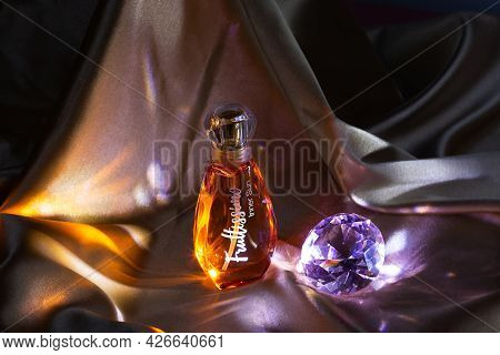 Moscow, Russia - July 12, 2021: A Bottle Of Toilet Water On A Gold Satin Fabric