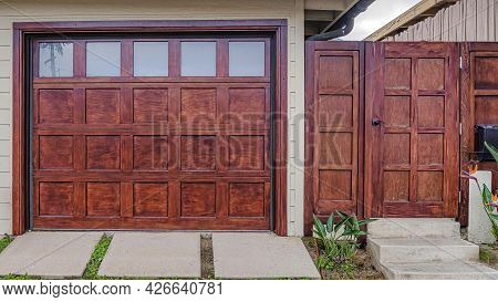 Pano Home In San Diego California With Glass Paned Garage Door Beside Wooden Gate