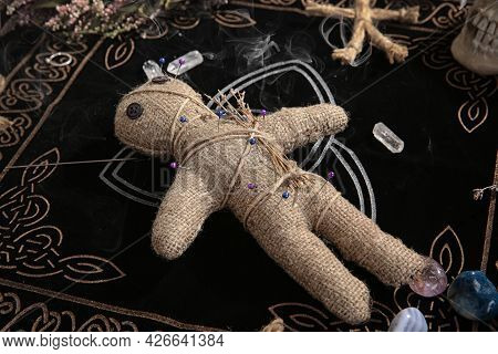 Voodoo Doll With Pins And Dried Flowers On Table