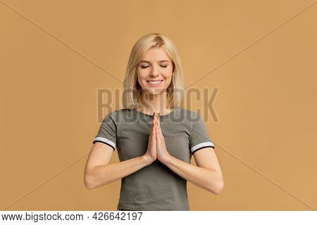 Portrait Of Peaceful Young Woman Praying With Clasped Hands And Closed Eyes, Blessed Female Feeling