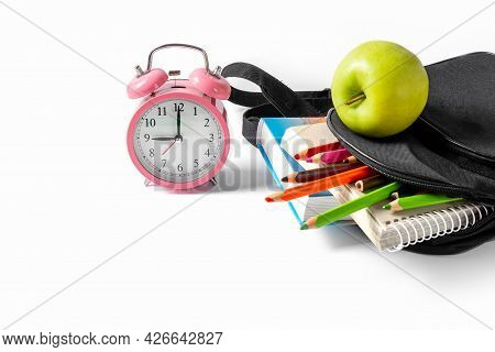 Alarm Clock, Green Apple And Open School Backpack On A White Background. Books, A Notebook And Penci