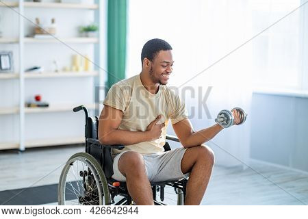 Physical Rehab For Impaired People. Positive Handicapped Black Man In Wheelchair Exercising With Dum
