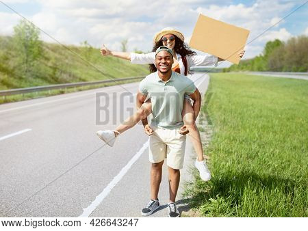 Full Length Of Happy Multiracial Couple Hitchhiking, Trying To Stop Car With Empty Cardboard Sign, M