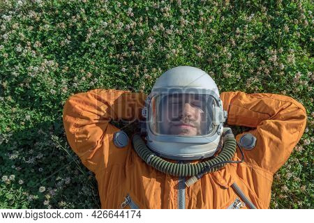 Astronaut Sleeping On Meadow. Closeup Of Cosmonaut Wearing Space Suit And Helmet Taking A Nap While