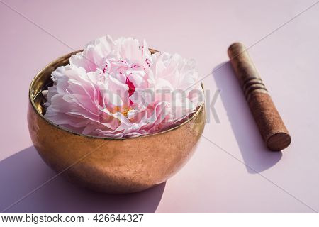 Tibetan Singing Bowl With Floating In Water Pink Peony Inside And Special Stick On The Pink Backgrou