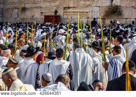 JERUSALEM, ISRAEL - SEPTEMBER 26, 2018: Morning autumn Sukkot. The area in front of Western Wall of Temple filled with people. The Jews of ritual clothes - tallit hold four ritual plants