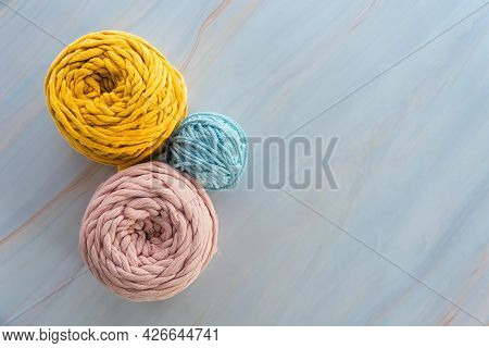 Top View Of Round Colorful Skeins Of Cotton Yarns For Macrame Knitting With Blank Space.