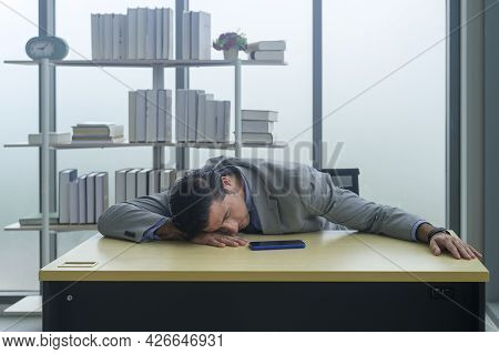A Young Businessman Tired And Exhausted At Work Place.