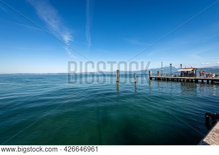 Lago Di Garda. Lake Garda From The Port Of The Small Town Of Lazise With The Pier For Ferry Docking,