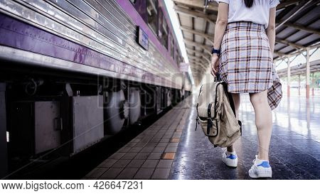 Young Woman Traveler With Backpack Walking At Train Station And Waits Train On Railway Platform. Tra