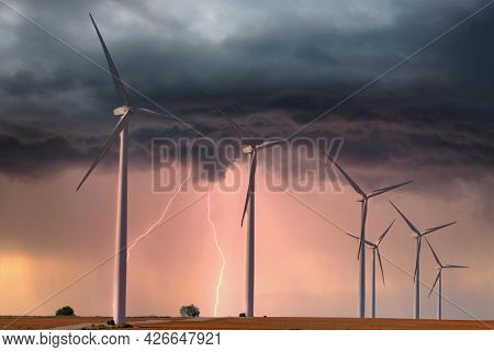 Modern windfarm located on farmland in midwest America during a lightening storm.