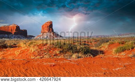Colorful rock formations with a dusting of snow in the Navajo Nation Park Monument Valley during a lightening storm