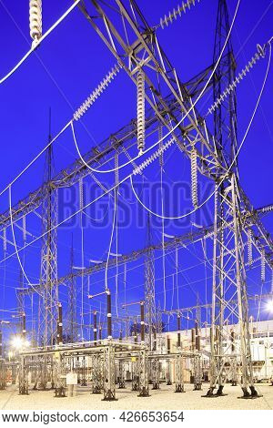 View Of An Illuminated Electricity Substation At Dusk.