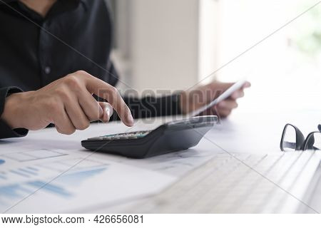 Business Accounting Concept, Business Man Using Calculator With Computer Laptop, Budget And Loan Pap