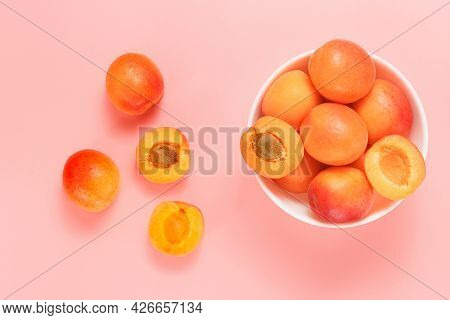 Bowl With Ripe Apricots And Sliced Apricots On The Pink Background, Summer Seasonal Healthy Fruits