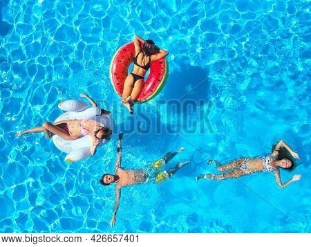 Aerial Of Friends Having Party In Swimming Pool With Inflatable Flamingo, Swan, Mattress. Happy Youn