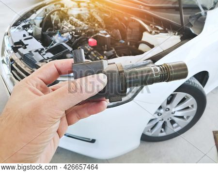 Ignition Coil For Spark Plug Of The Car Ignition System In The Mechanic Hand With A Car Blurred Back