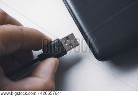 Hand Inserting Usb (universal Serial Bus) Type A Version 3.0 Connecting To Usb Port Of Laptop