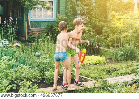 Two Little Boys Playing With Water Guns On Hot Summer Day. Cute Children Having Fun With Water On Th