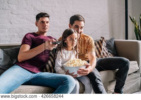 Two Parents And Their Daughter Watching A