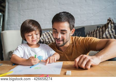 Father And Son Playing Together At Home.