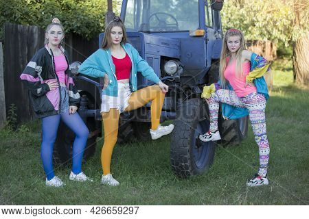 Three Country Girls Dressed In The Style Of The 90s Stand By The Tractor.