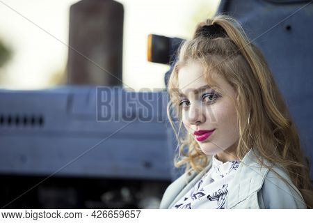 A Beautiful Country Girl In The Style Of The 90s In Bright Clothes Stands Near A Tractor.