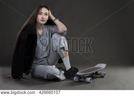 Beautiful Girl Model With A Skateboard In A Photo Studio.