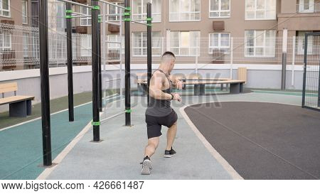 A Sports Guy On A Sunny Day Does A Warm-up On An Open Sports Ground In Summer. The Athlete Does A Wa