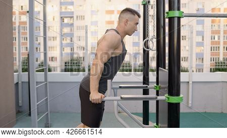 Young Man Workout Out Arms On Dips Horizontal Bars Training Triceps And Biceps Doing Push Ups Outdoo