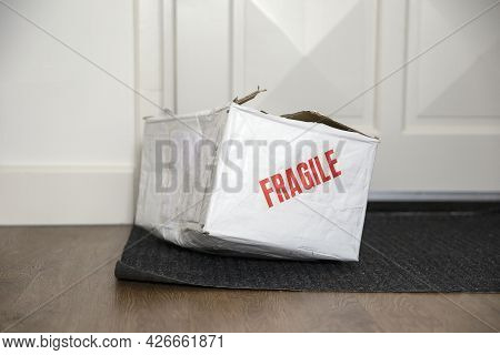 Beat Up Damaged Delivery Box With Fragile Sticker, Broken Deliverd Cardboard Packaging At Home