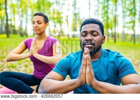 An Attractive Young Woman And Man Doing Yoga In Green Forest