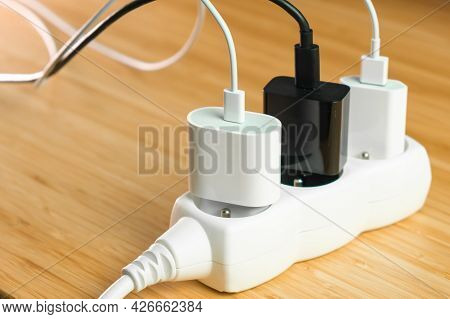 The Electrical Extension Strip With Connected White And Black Power Plugs On The Wooden Table. Smart