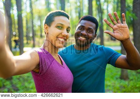 Latin American Couple Ready To Yoga Time Outdoors Pink And Blue Look Taking Self Portrait On Modern