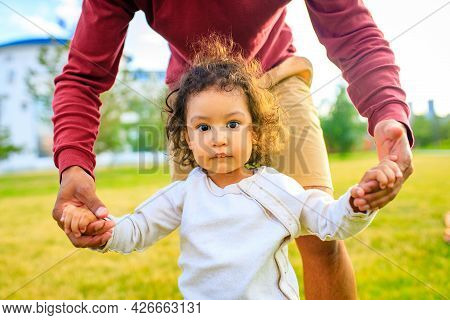 Young Pretty Dad And His Little Curly Daughter Walk Together Outdoors At Sunset Light