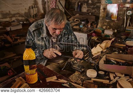 A Mature Wood Craftsman Saws A Piece Of Wood Clamped In A Vice With A Hacksaw. Craftsman Making Hand