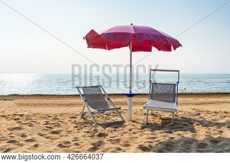 Sunbeds And Parasol Beach Umbrella At The Sunny Beach In Italy. Recreation At The Idyllic Touristic