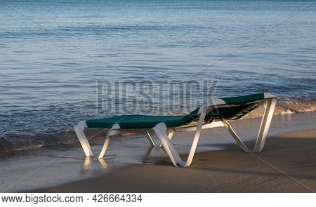 Sun Loungers Stand On A Sandy Beach By The Sea