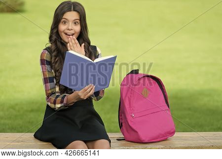 Finding Inspiration In Reading. Surprised Child Read Book Sitting On Park Bench. Inspiration Concept