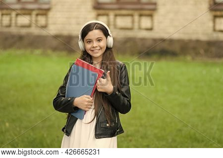 Best Technology Available. Happy Child Give Thumbs Up Outdoors. Little Kid Listen To Music In Headph