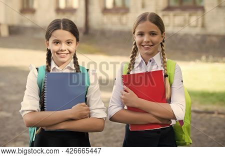 Have Fun While Studying. Happy Girls In School Uniform. Smiling Teen Students With Backpack Holding