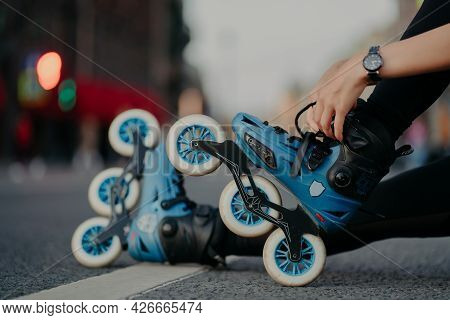 Cropped Shot Of Unrecognizable Woman Puts On Rollerblades Poses Outdoors On Asphalt Against Blurred
